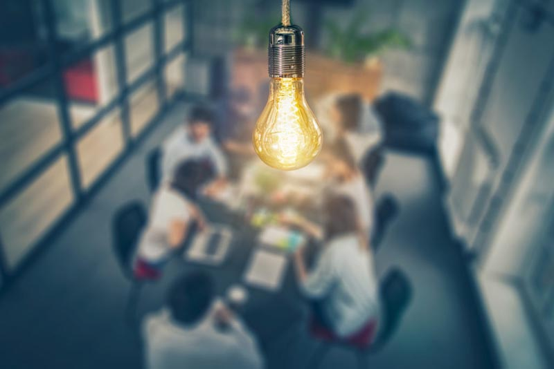 lightbulb representing ideas and innovation hanging over a technology team meeting