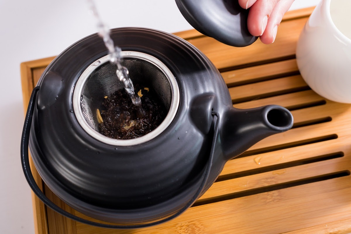 a wooden tray with a teapot on a quartz countertop