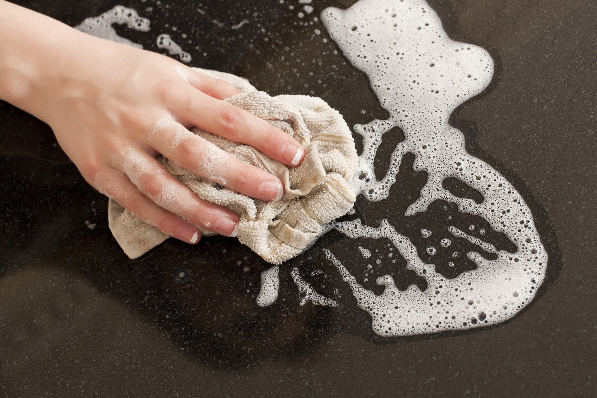 a woman's hand wiping a quartz countertop with a cloth