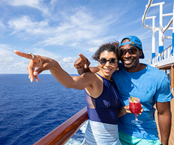Happy couple on cruise ship pointing at the view