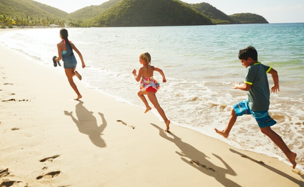 Three kids running across the sand on a Caribbean beach