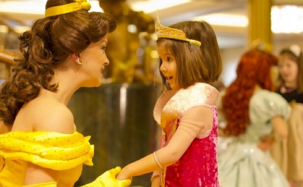 Woman in Princess Belle costume smiling with young girl