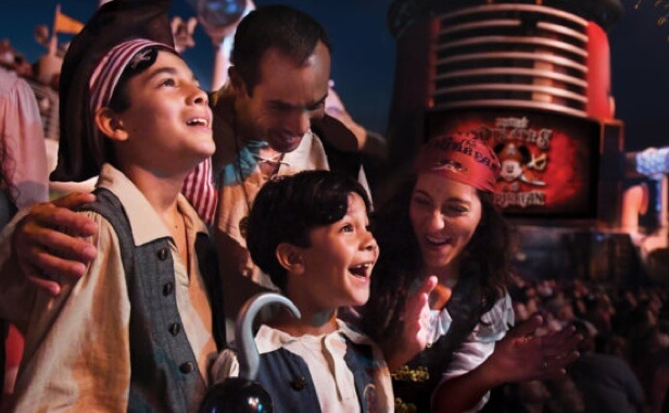 Young boys dressed as pirates enjoying a live show with parents