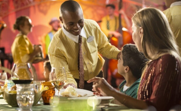 Male cruise staff serving a mother and her son at dinner