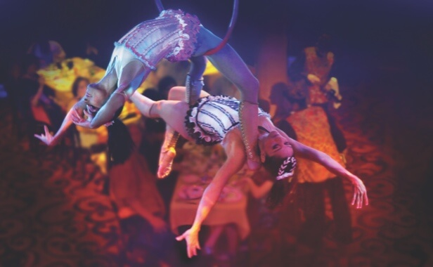 Two female acrobats intertwined in the air during a performance