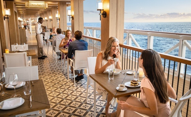 Cruise ship guests enjoying al fresco dining in an understated atmosphere onboard