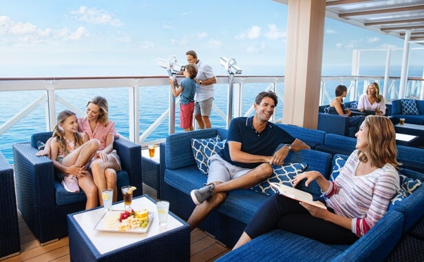 Family enjoying cushy outdoor seating on a cruise