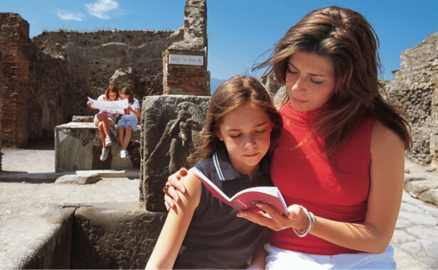Woman and daughter viewing guidebook near ruins