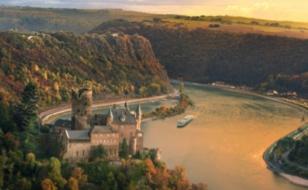 Viking longship sailing down a river past a castle on a cliff