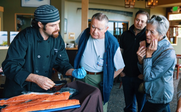 Chef preparing salmon with guests