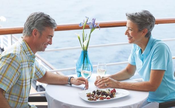 Couple enjoying a meal on their cruise balcony