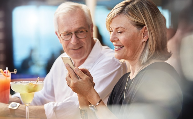 Woman smiling at her phone as her husband smiles with her