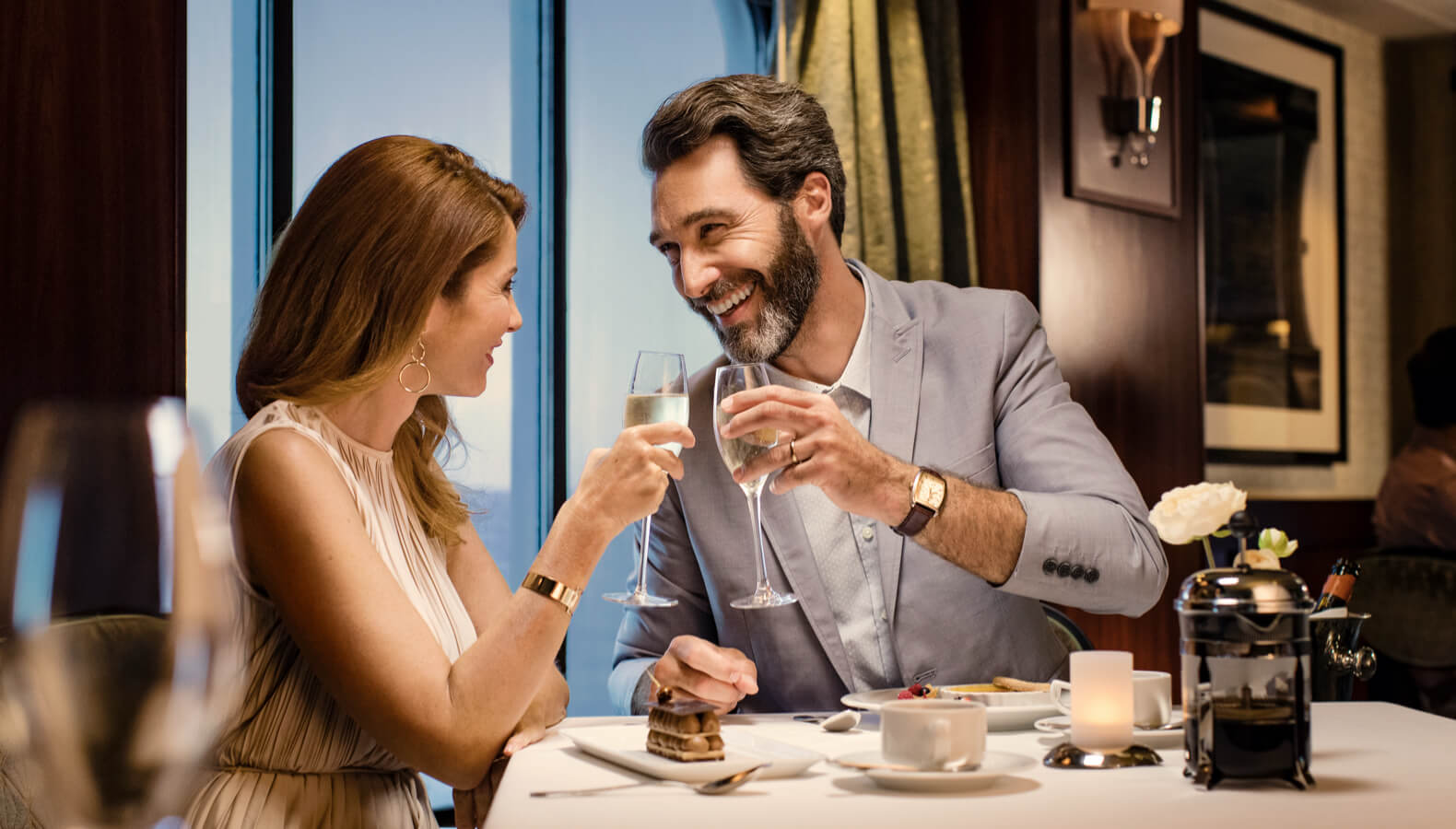 Couple toasting at restaurant on ship