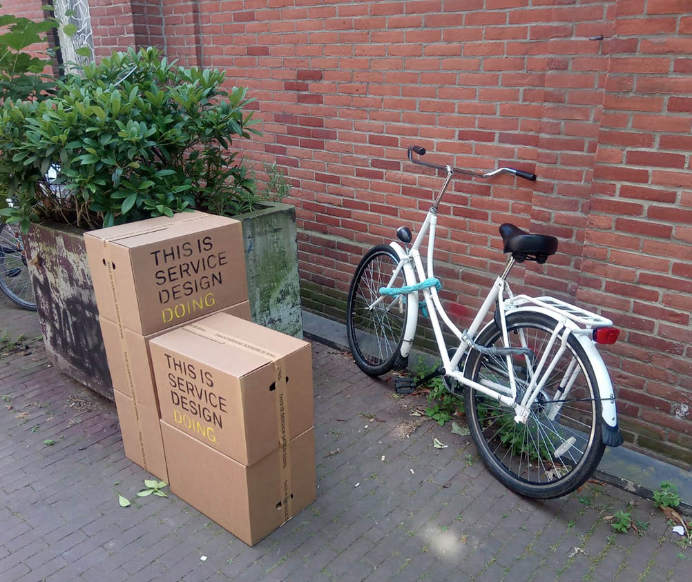Photo of a bike in our office yard, some spray-painted This is Service Design Doing boxes in the front