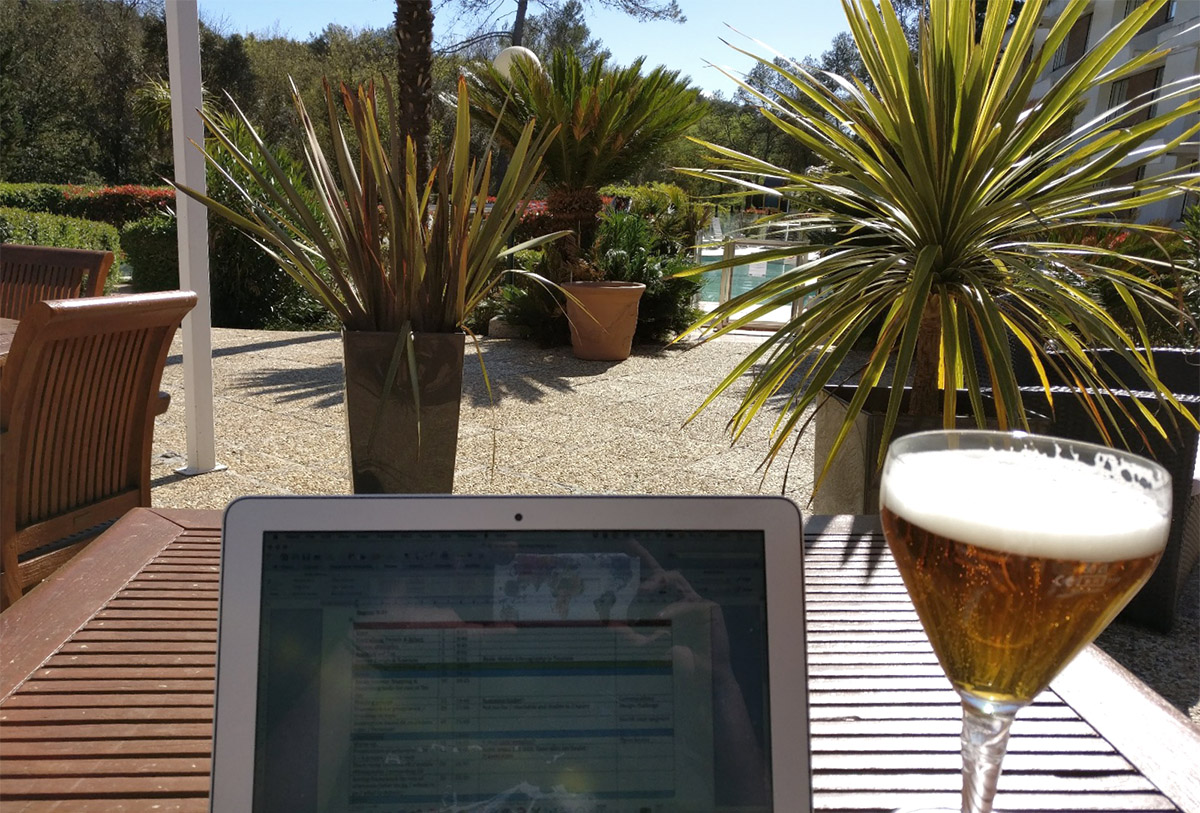 Photo of a laptop in a holiday-looking environment with palm trees and a beer on the desk