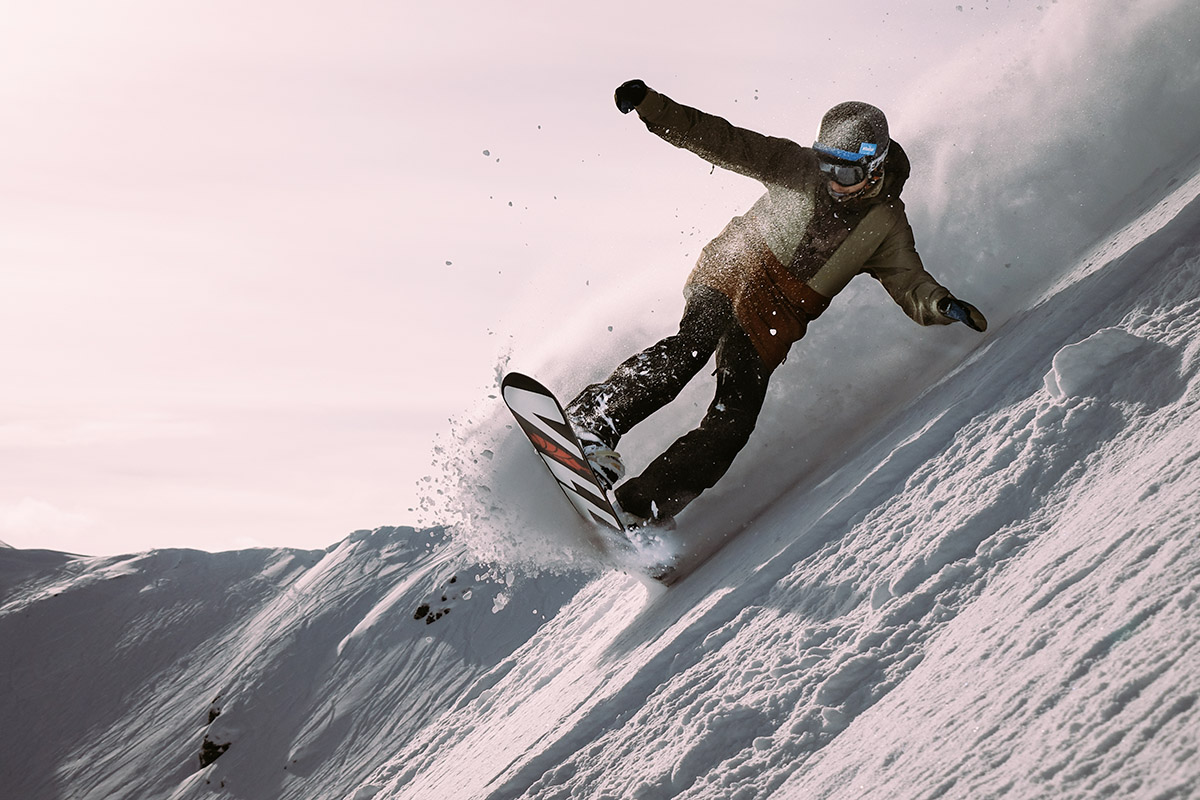 Photo of a snowboarder in powder snow, going downhill