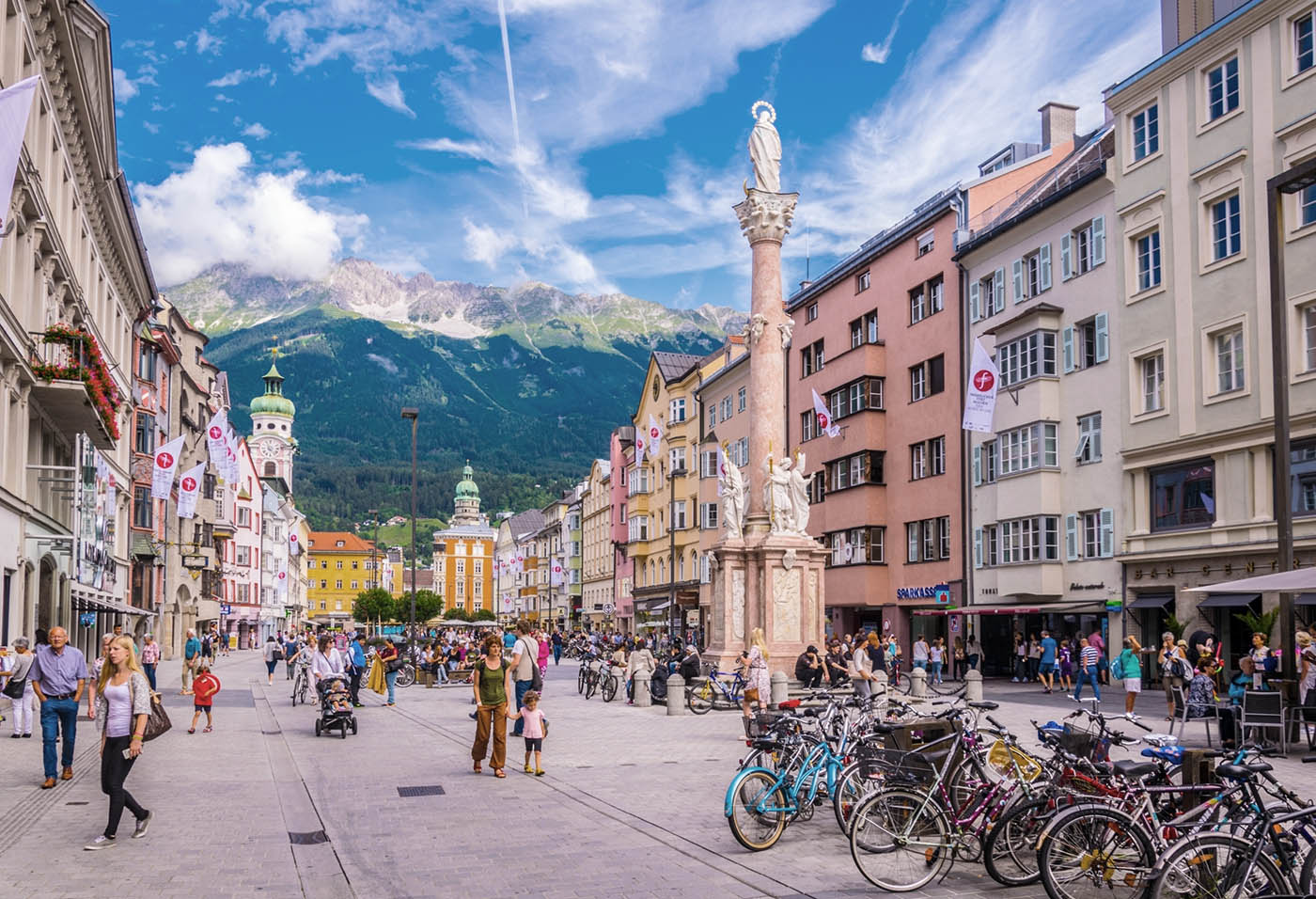 Photo of Innsbruck's Theresienstrasse, with mountains of Nordkette in the background. It's real but it looks like a tourist postcard.