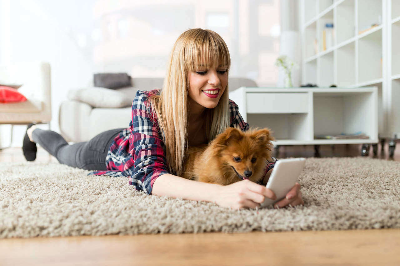 girl using phone with dog