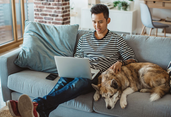 Man sits on the sofa with his dog, consults the earnings going in his JustPark account