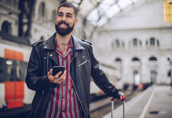 Man at train station with a mobile phone