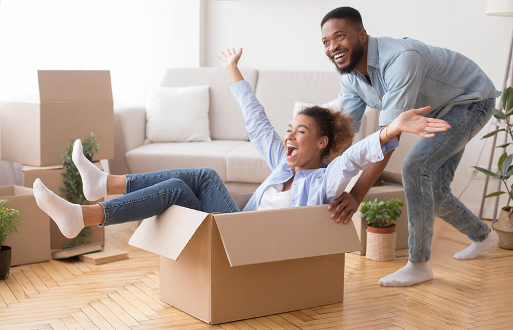 excited-man-riding-woman-in-moving-box-in-new-hous