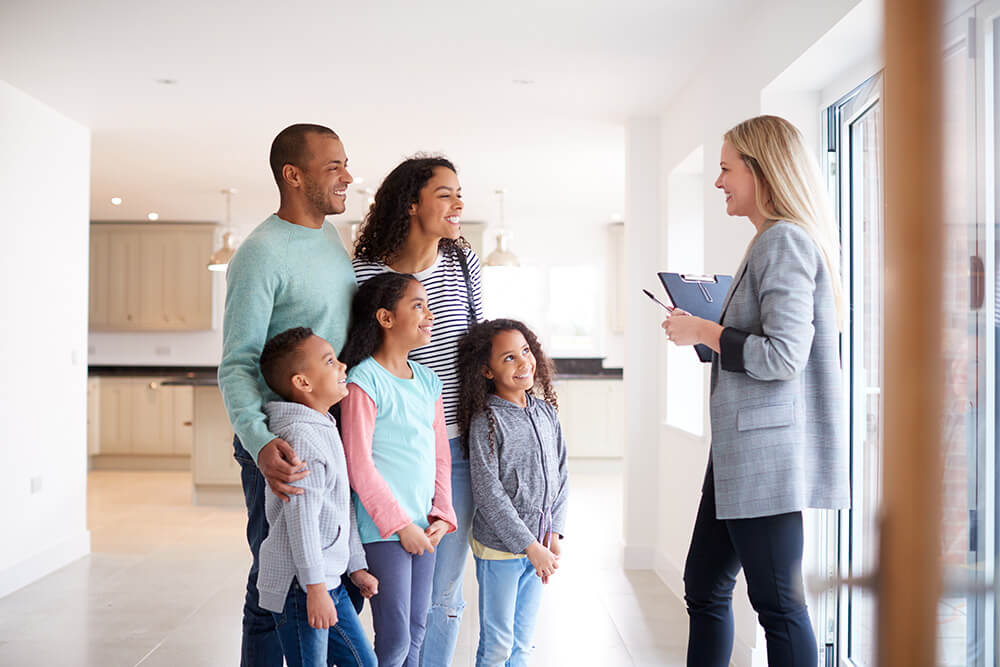 female-realtor-showing-family-interested-in-buying