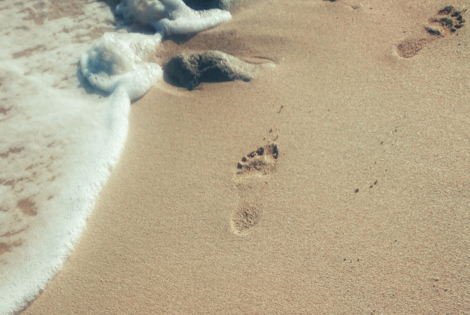 A carbon footprint being symbolized by footprints in the sand on a beach.