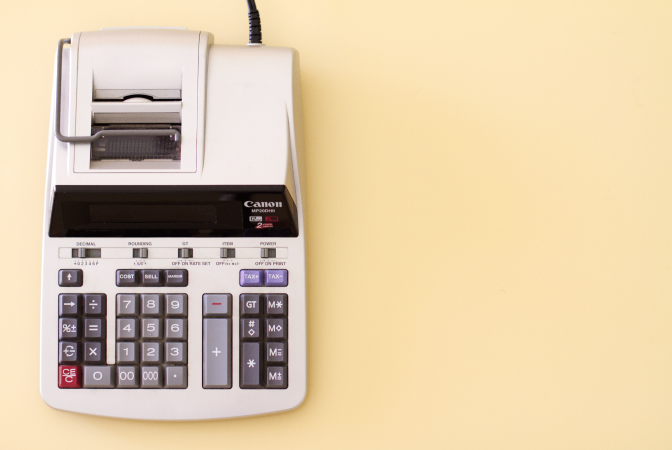Calculating carbon footprints symbolized by an old financial calculator.