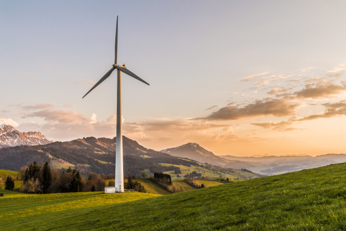 Wind turbine with a lush mountain background