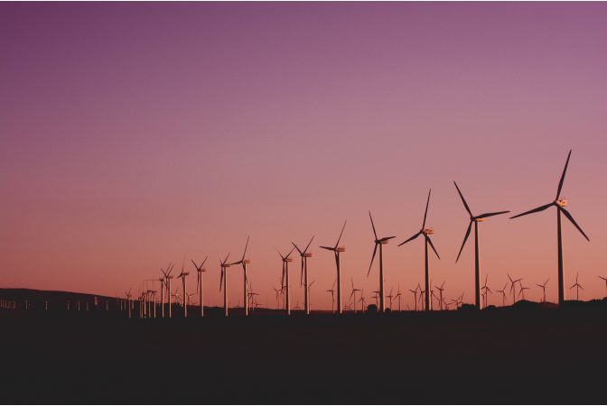 A line of Wind turbines against a pink sky