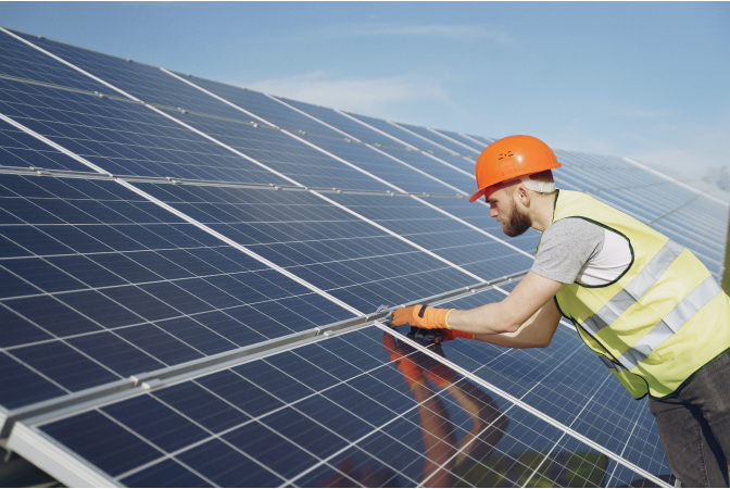 Man in orange hardhat leaning over a large bank of solar panels