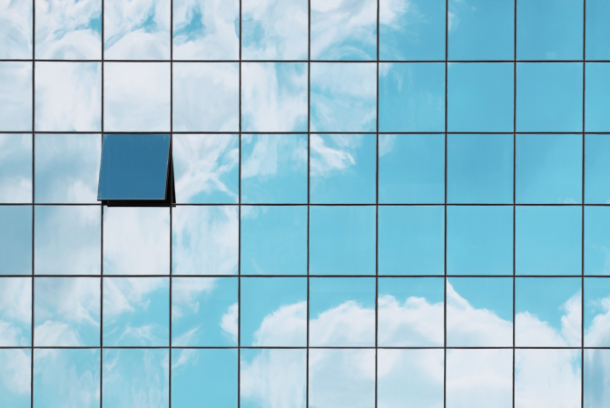 Skyscraper windows reflecting the sky and clouds