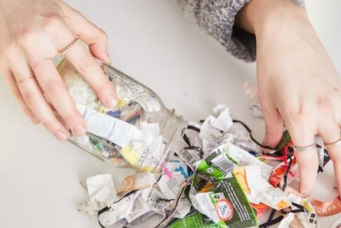 Hands emptying a mason jar of garbage