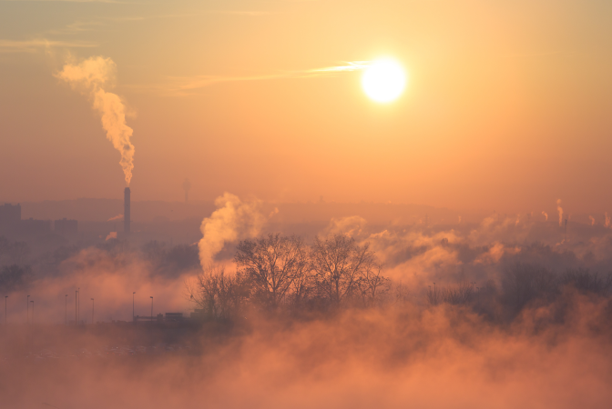 A factory burning fossil fuels causing smoke and pollution