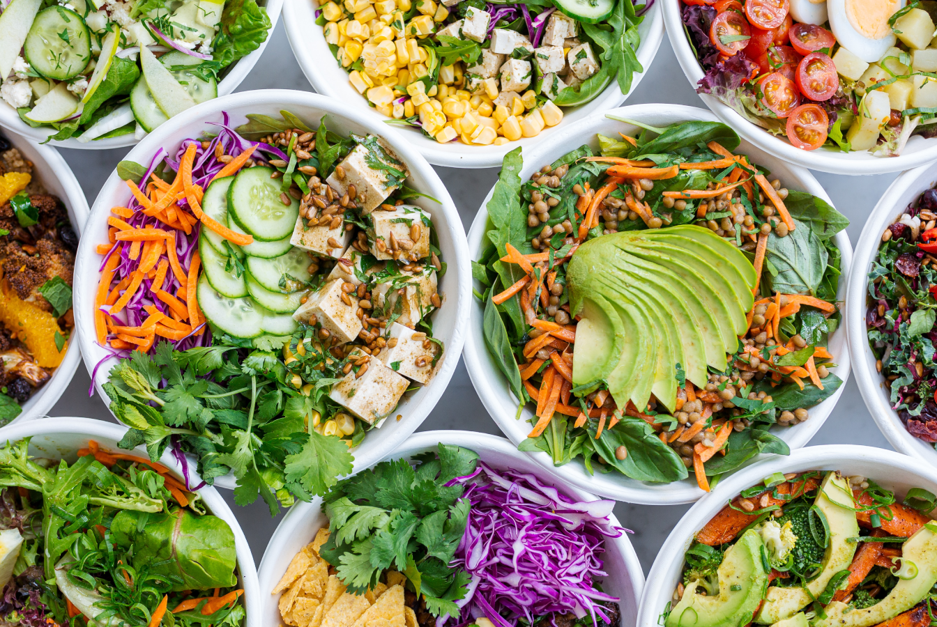Top view of assorted vegetarian salads in bowls, all of which can be eaten as part of a plant-based diet.