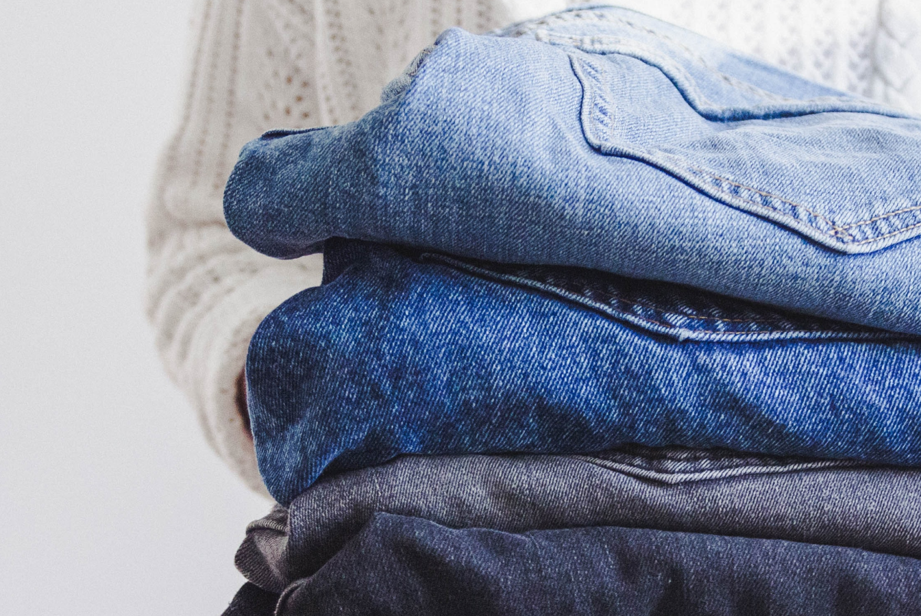 Person carrying stack of folded jeans