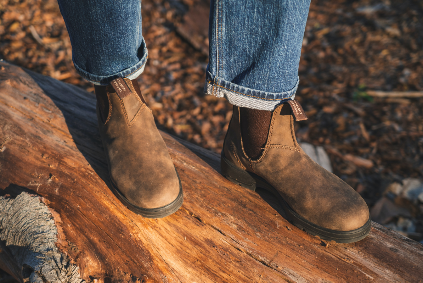 Person in leather boots standing on a log in the woods
