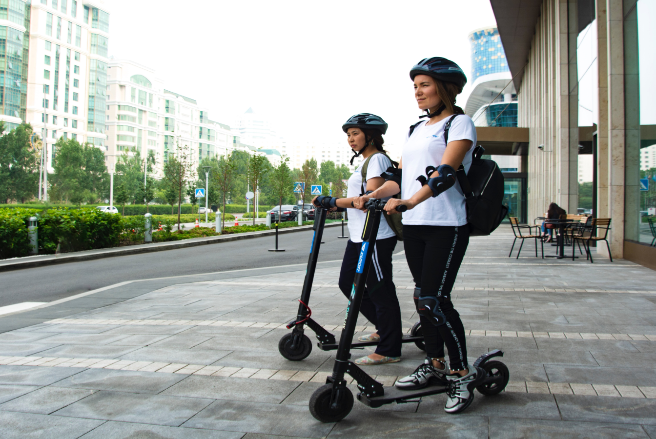 Two people on electric scooters carrying bags