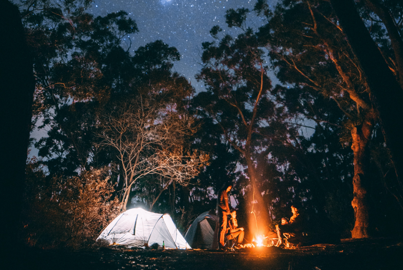 Four campers around a fire a night with a tent