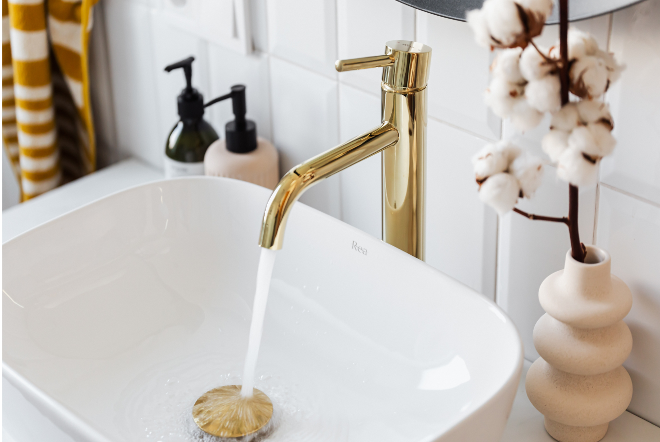 Gold faucet running into white porceline sink
