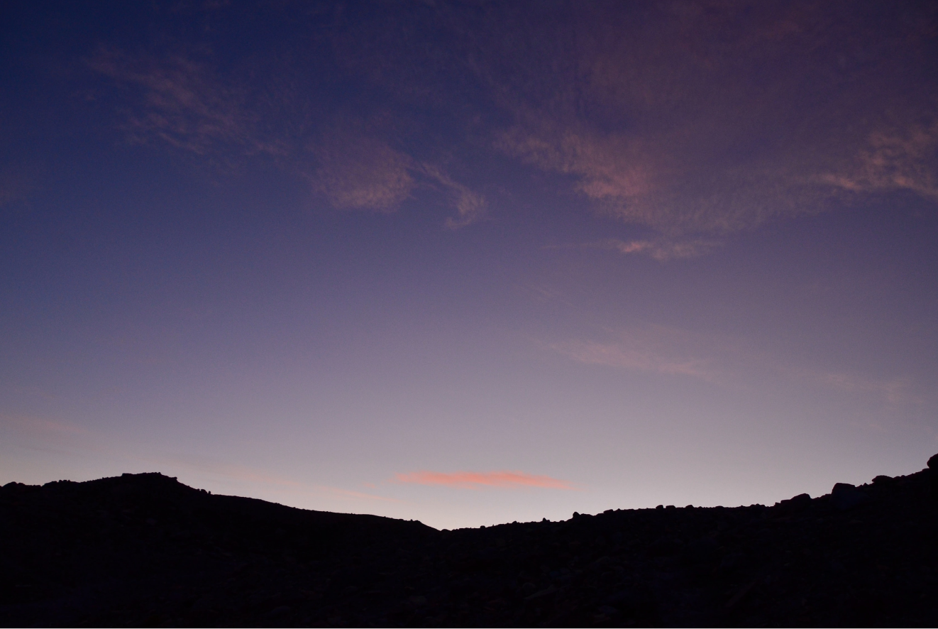 Mountains backlit by pink and purple sunset