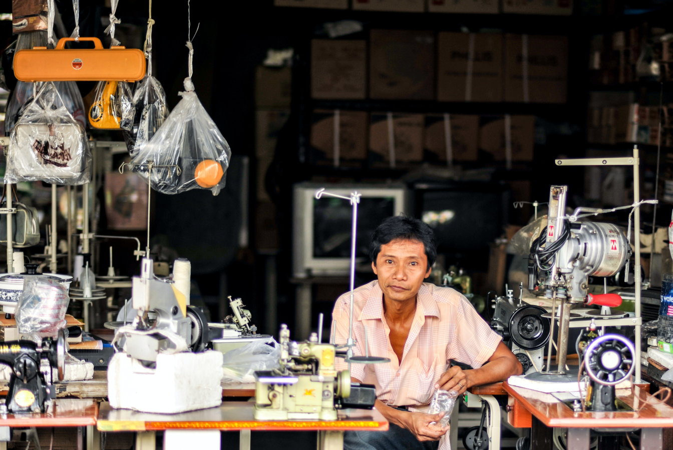 Older man sitting at a bank of sewing machines