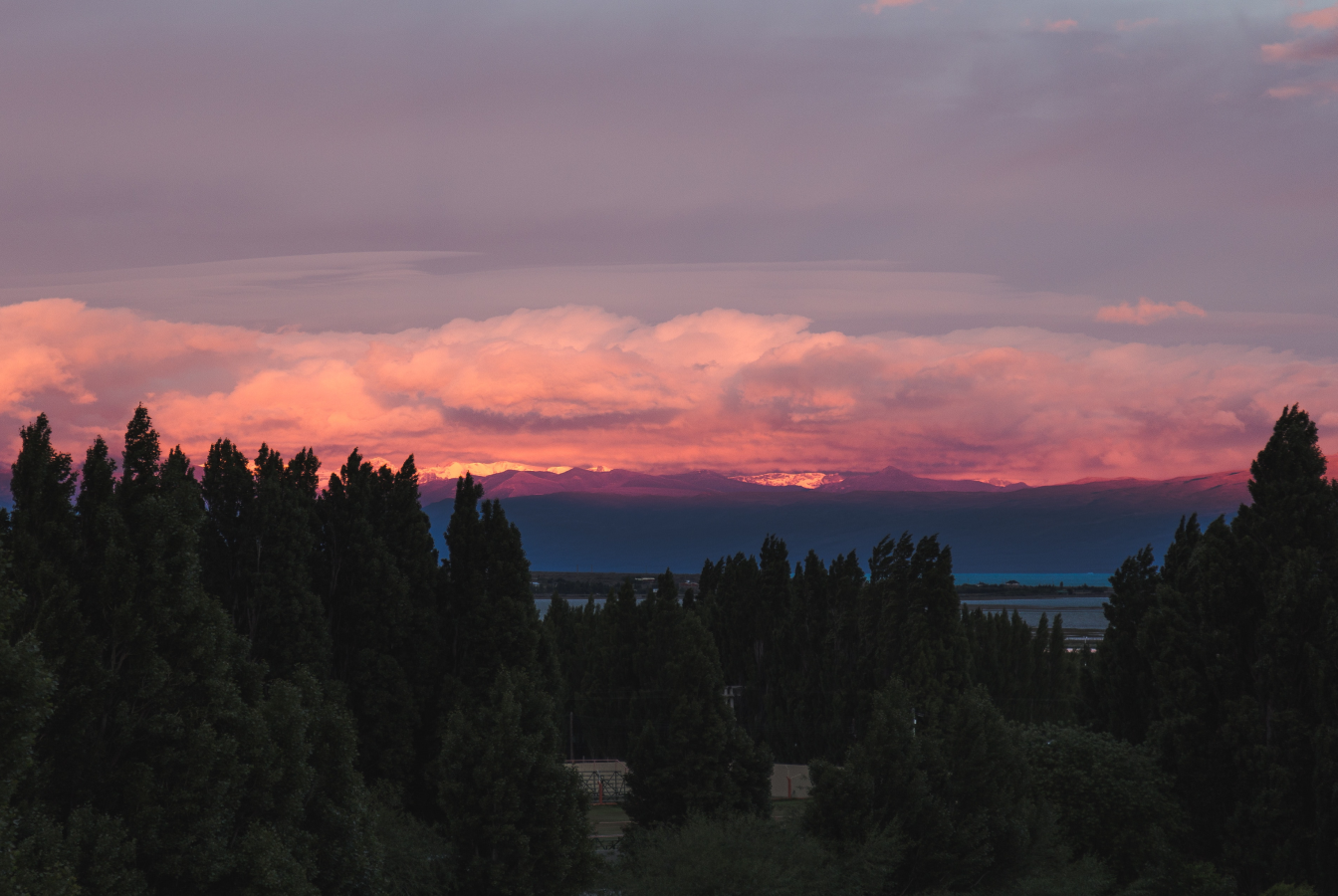 Sun setting behind snowy mountains clouds, overhead