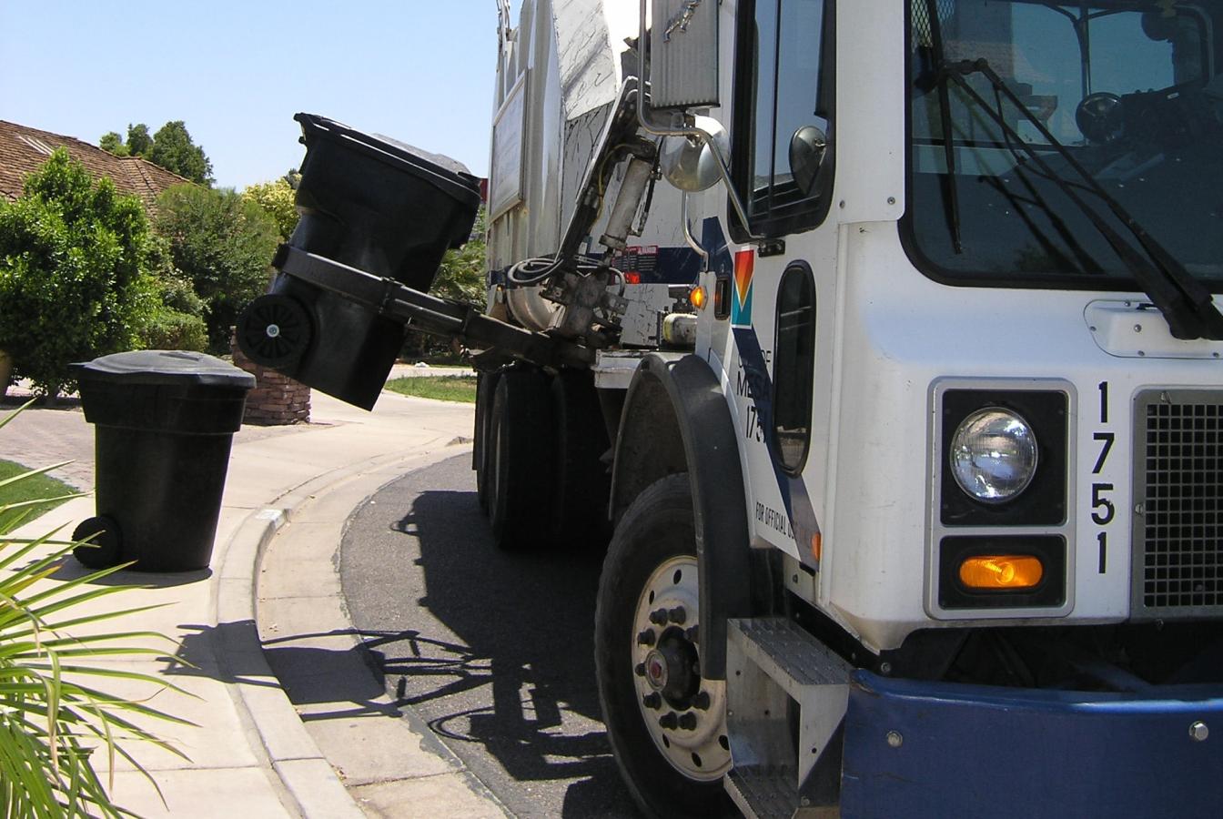 Mechanized garbage truck picking up bin