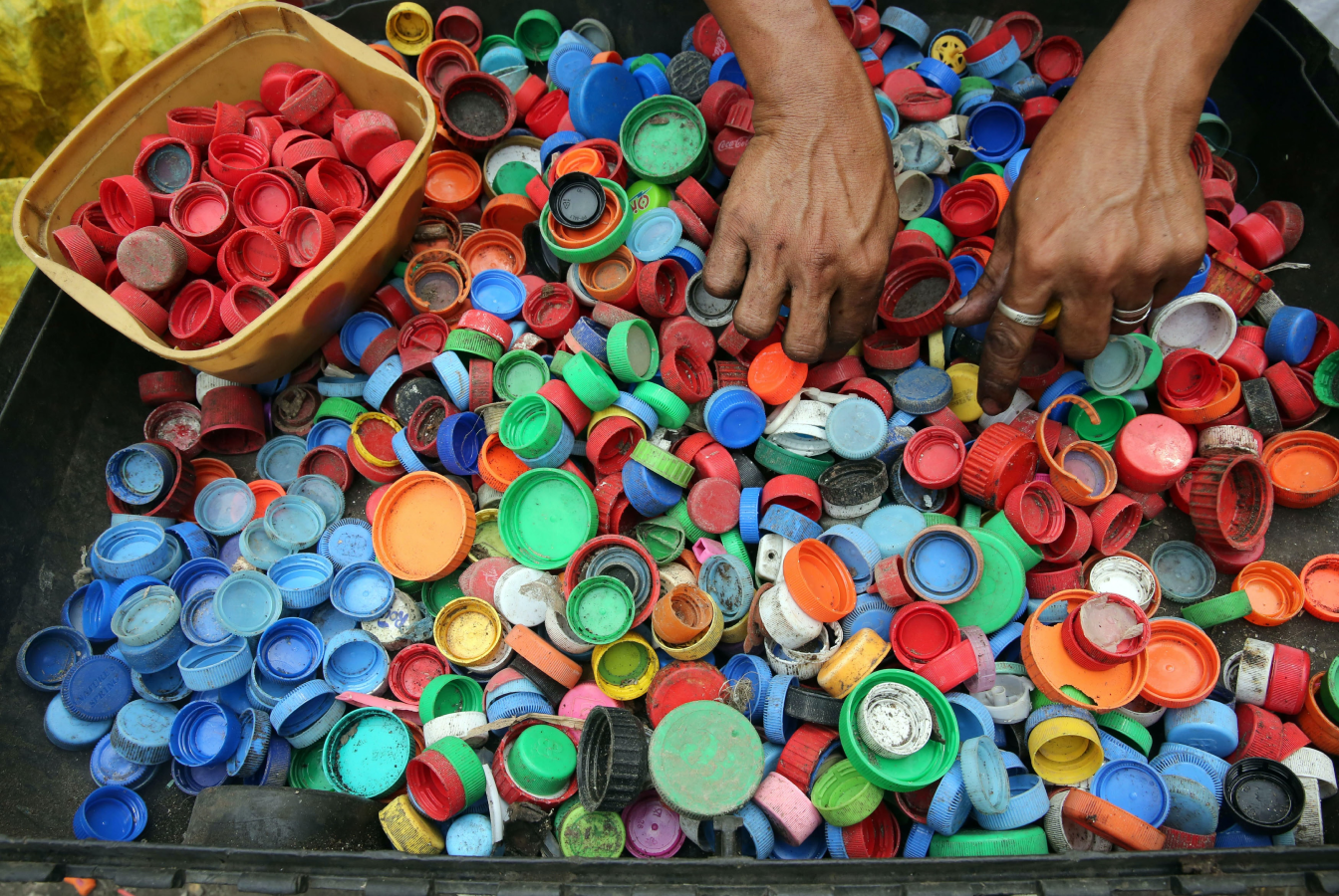 Pair of hands sorting plastic bottle caps
