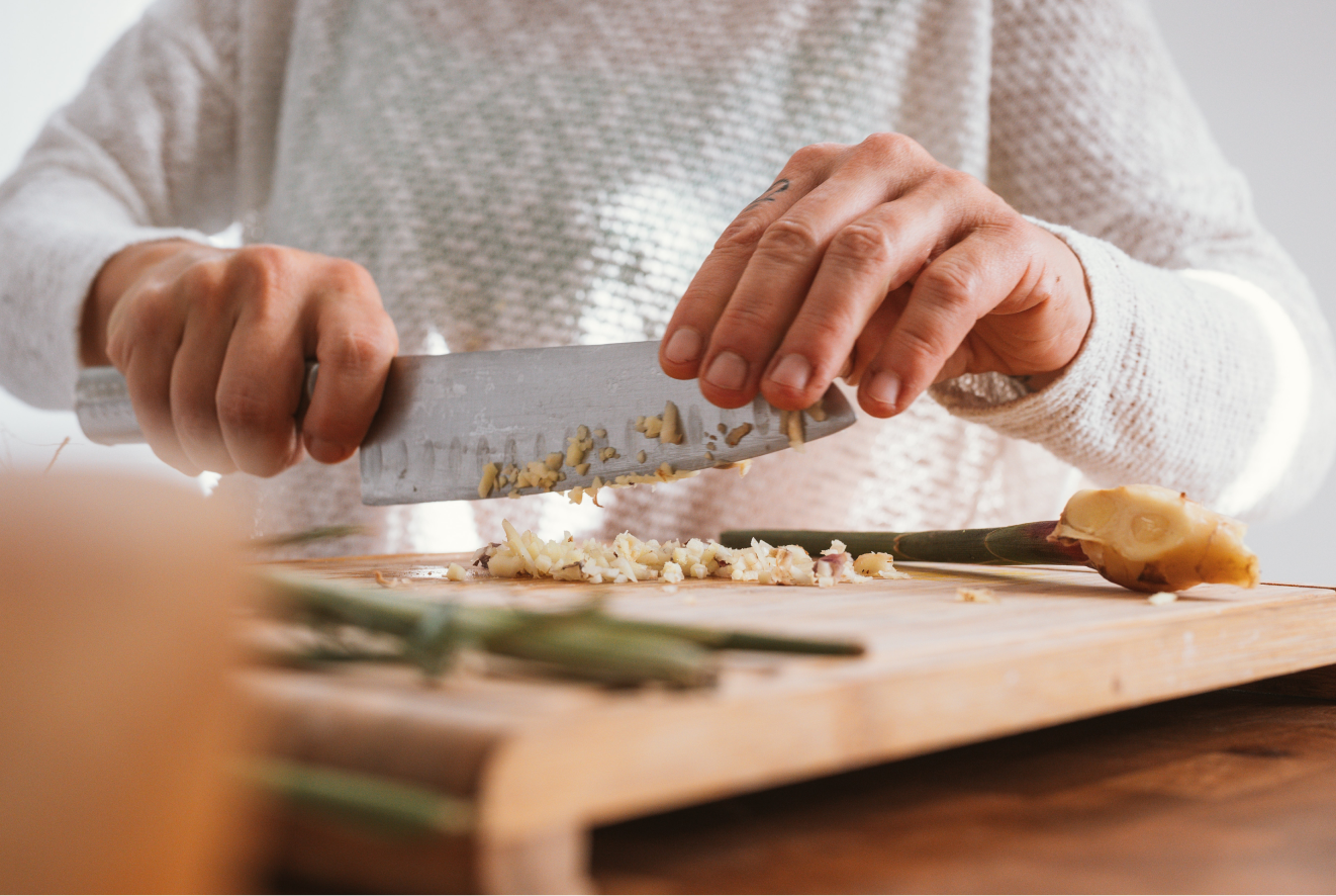 A person chopping raw ginger for a vegan dish