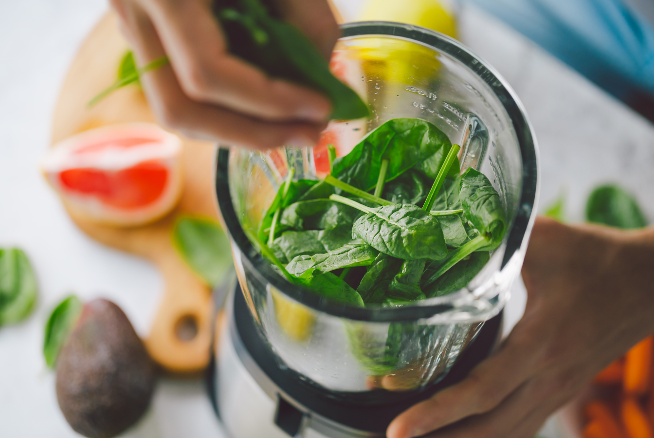 Spinach being blended for a plant-based smoothie