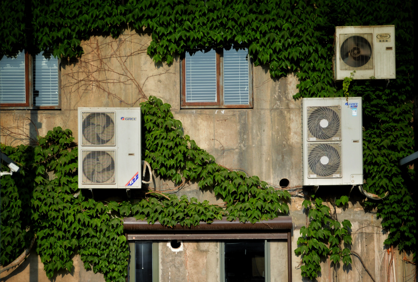 Air conditioning units on the side of a building, contributing to climate change.