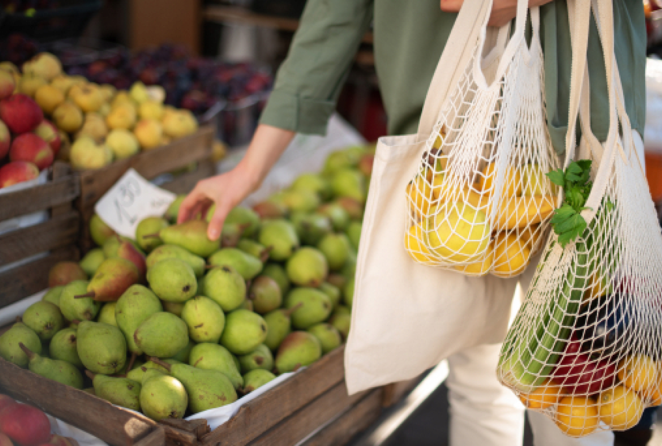 A lady using tote bags rather than plastic ones to buy produce.