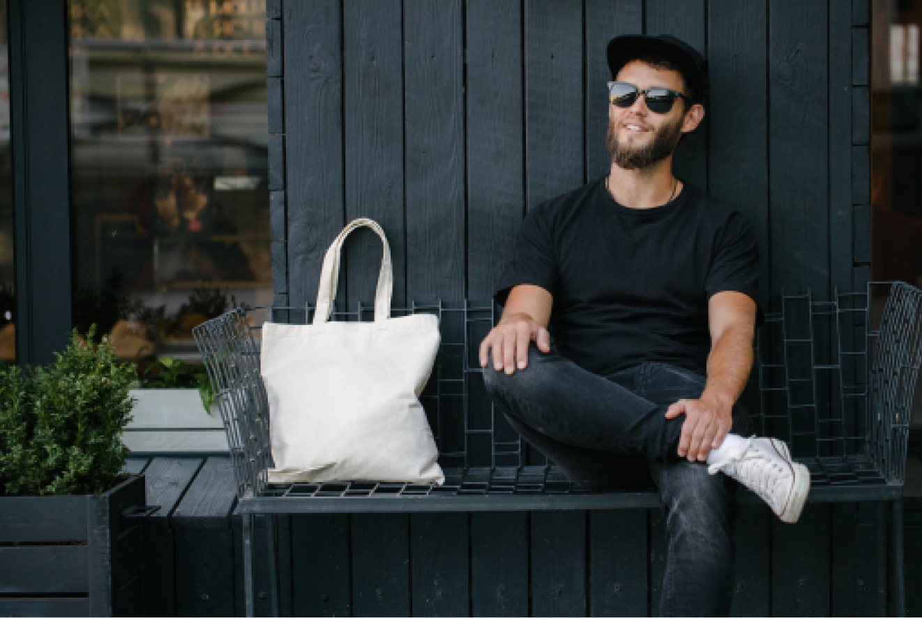A guy sitting next to his tote bag on a bench.
